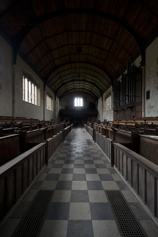 Inside the chapel, complete with pews and pipe organ.